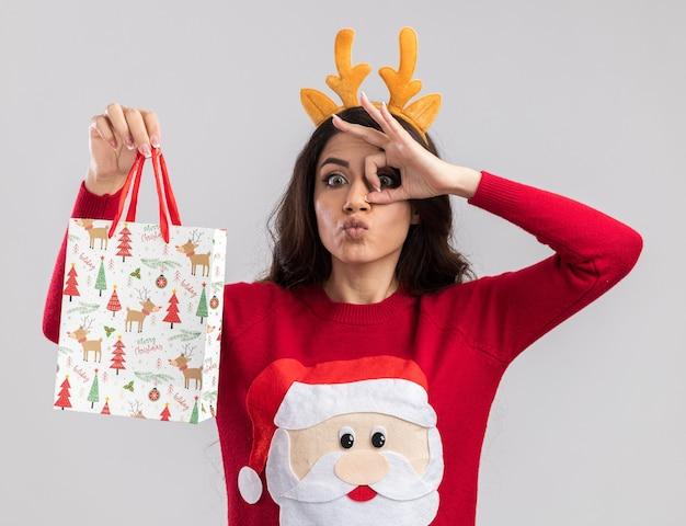Pod wrażeniem młoda ładna dziewczyna w opasce z poroża renifera i swetrze świętego mikołaja trzyma torbę z prezentami świątecznymi patrząc na kamerę, robi gest spojrzenia na białym tle