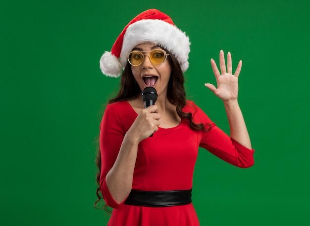 Pod wrażeniem młoda ładna dziewczyna w santa hat i okularach trzymająca mikrofon, trzymająca rękę w powietrzu, rozmawiająca do mikrofonu na zielonej ścianie z kopią miejsca