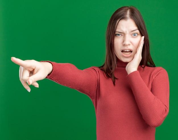 Pod wrażeniem młoda ładna dziewczyna wskazująca na bok trzymająca rękę w pobliżu ust szepczących