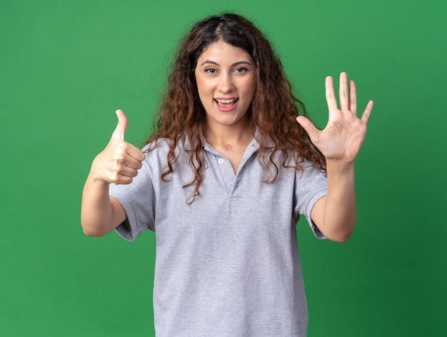 Pod wrażeniem młoda ładna kaukaska dziewczyna pokazująca sześć z rękami