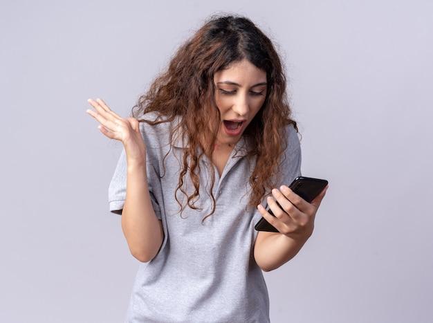Pod wrażeniem młoda ładna kaukaska dziewczyna trzymająca i patrząca na telefon komórkowy pokazujący pustą rękę odizolowaną na białej ścianie z miejscem na kopię