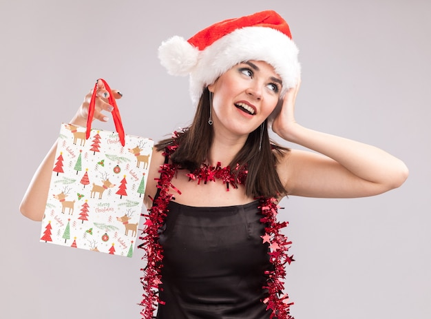 Pod wrażeniem młoda ładna kaukaska dziewczyna ubrana w santa hat i blichtr wianek wokół szyi trzymająca świąteczną torbę na prezent dotykając głowy patrząc na bok na białym tle