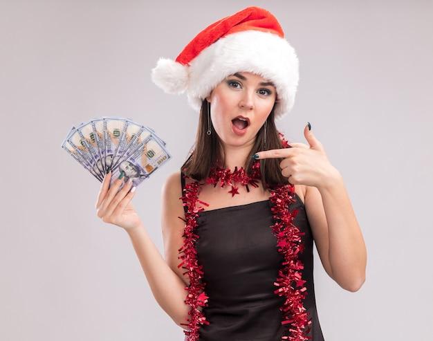 Pod wrażeniem młoda ładna kaukaska dziewczyna ubrana w santa hat i girlandę z świecidełkami wokół szyi, trzymająca i wskazująca na pieniądze patrząc na kamerę na białym tle