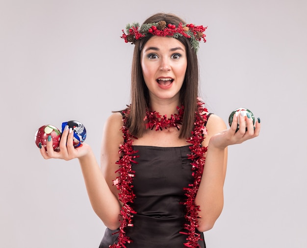 Pod wrażeniem młoda ładna kaukaska dziewczyna ubrana w świąteczny wieniec z głowy i blichtrową girlandę wokół szyi trzymającej bombki patrząc na kamerę na białym tle