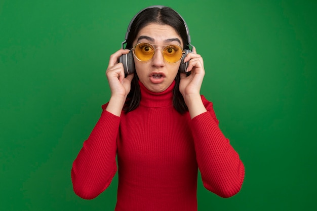 Pod wrażeniem młoda ładna kaukaska dziewczyna w okularach przeciwsłonecznych i słuchawkach, chwytająca słuchawki, patrząca prosto na zieloną ścianę z miejscem na kopię