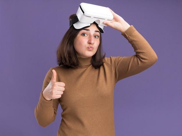 Pod wrażeniem młoda ładna kaukaska dziewczyna z beretowym kapeluszem trzyma zestaw słuchawkowy vr i kciukami w górę na fioletowej ścianie z miejsca na kopię