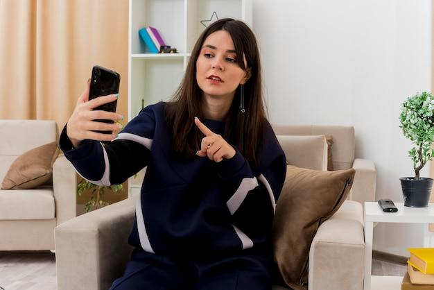 Pod wrażeniem młoda ładna kaukaska kobieta siedzi na fotelu w zaprojektowanym salonie trzymając telefon komórkowy i wskazując na niego, patrząc na niego