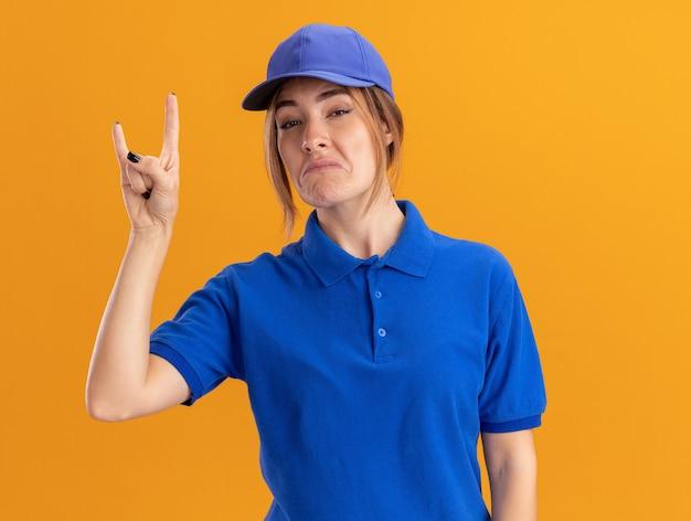 Pod wrażeniem młoda ładna kobieta dostawy w mundurze gesty rogi ręka znak na białym tle