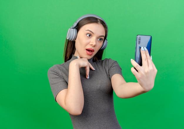 Pod wrażeniem młoda ładna kobieta nosi słuchawki, trzymając i patrząc na telefon komórkowy i trzymając rękę na klatce piersiowej na białym tle na zielonym tle z miejsca na kopię