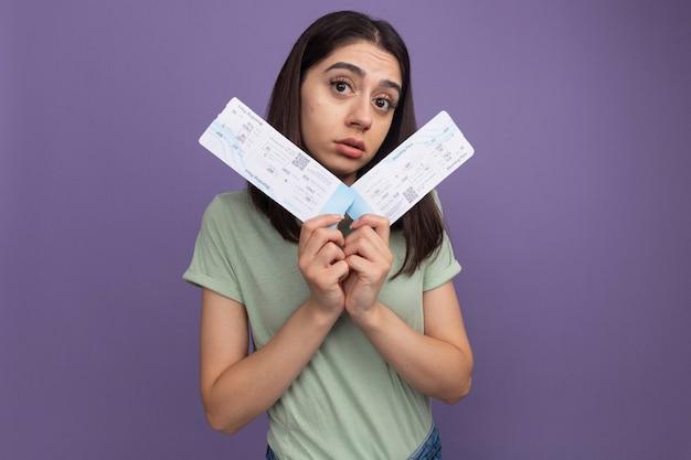 Pod wrażeniem młoda ładna kobieta patrząca na przód trzymająca bilety lotnicze patrząca na przód odizolowana na fioletowej ścianie z kopią miejsca