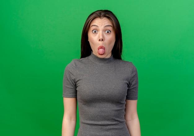 Pod wrażeniem młoda ładna kobieta pokazuje język w aparacie odizolowane na zielono z miejsca na kopię