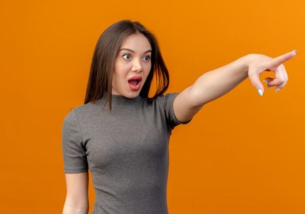 Pod wrażeniem młoda ładna kobieta szuka i wskazuje prosto na pomarańczowo