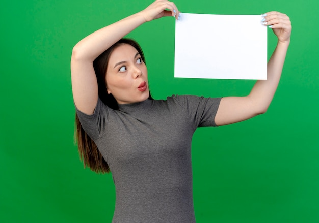 Pod wrażeniem młoda ładna kobieta trzyma i patrząc na papier na białym tle na zielonym tle