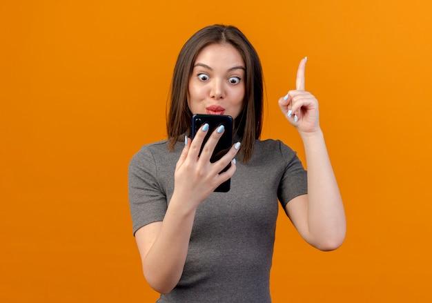 Pod wrażeniem młoda ładna kobieta trzyma i patrząc na telefon komórkowy i podnosząc palec na białym tle na pomarańczowym tle z miejsca na kopię