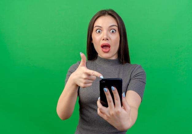 Pod wrażeniem młoda ładna kobieta trzyma i wskazuje na telefon komórkowy na białym tle na zielonym tle z miejsca na kopię