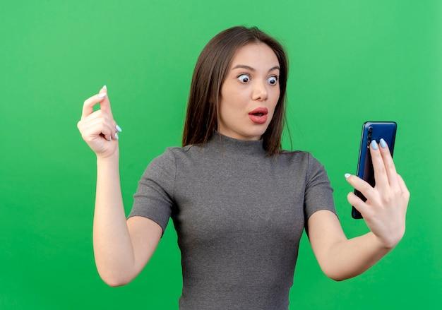 Pod wrażeniem młoda ładna kobieta trzyma telefon komórkowy i patrząc na niego i trzymając rękę w powietrzu na białym tle na zielonym tle