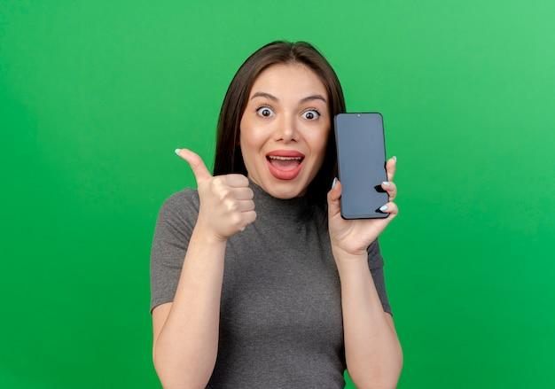 Pod wrażeniem młoda ładna kobieta trzyma telefon komórkowy i pokazuje kciuk do góry na białym tle na zielonym tle z miejsca na kopię
