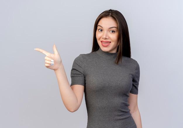 Pod wrażeniem młoda ładna kobieta, wskazując na boku na białym tle