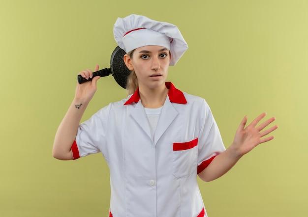 Pod wrażeniem młoda ładna kucharka w mundurze szefa kuchni trzymająca patelnię za głową i pokazująca pustą rękę odizolowaną na zielonej ścianie
