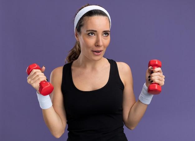Pod wrażeniem młoda, ładna sportowa dziewczyna nosząca opaskę na głowę i nadgarstki trzymająca hantle patrząca w górę