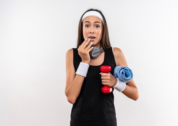 Pod wrażeniem młoda ładna sportowa dziewczyna ubrana w opaskę i opaskę na rękę i słuchawki na szyi, trzymając hantle z ręcznikiem, kładąc rękę na brodzie na białym tle na białej ścianie z miejscem na kopię