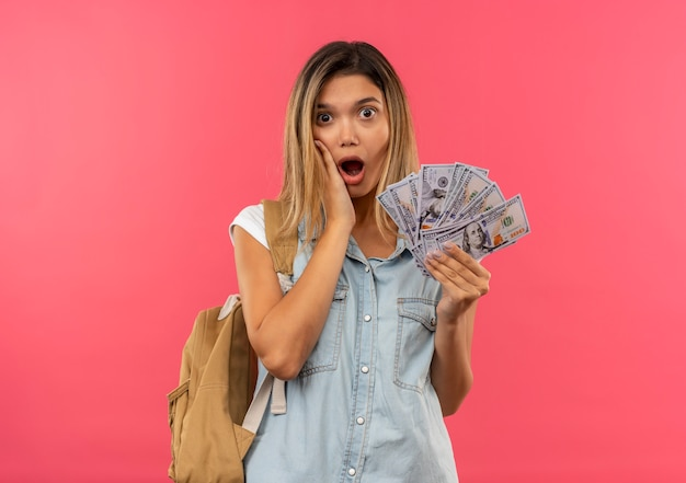 Pod wrażeniem młoda ładna studencka dziewczyna ubrana w tylną torbę, trzymając pieniądze i kładąc rękę na policzku na różowym tle
