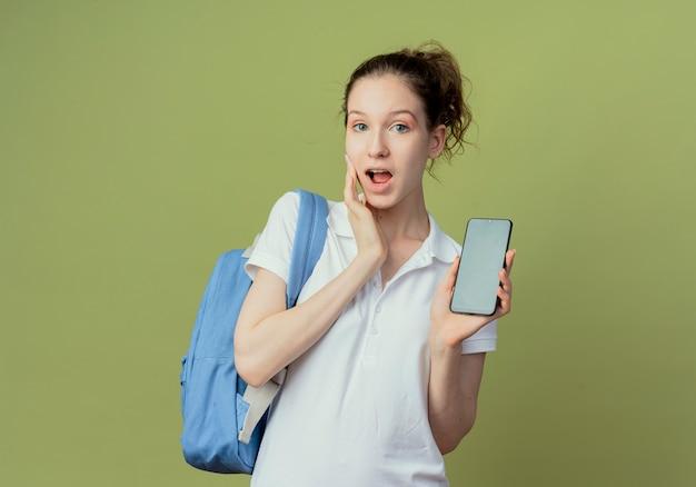 Pod wrażeniem młoda ładna studentka na sobie tylną torbę pokazując telefon komórkowy i dotykając twarzy na białym tle na zielonym tle z miejsca na kopię