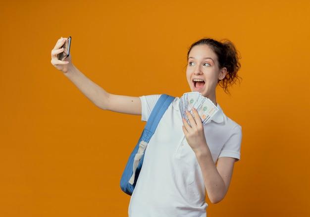 Pod wrażeniem młoda ładna studentka na sobie tylną torbę, trzymając pieniądze i biorąc selfie na białym tle na pomarańczowym tle
