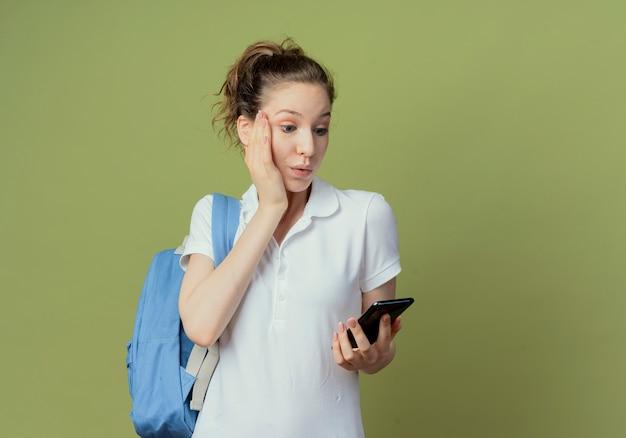 Pod wrażeniem młoda ładna studentka nosząca tylną torbę, trzymając i patrząc na telefon komórkowy i kładąc dłoń na twarzy na białym tle na zielonym tle z miejscem na kopię