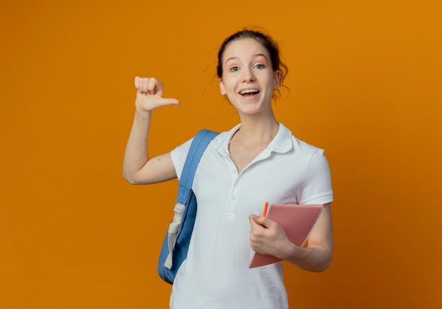 Pod wrażeniem młoda ładna studentka noszenie plecaka trzymając notes i pióro, wskazując na siebie na białym tle na pomarańczowym tle z miejsca na kopię