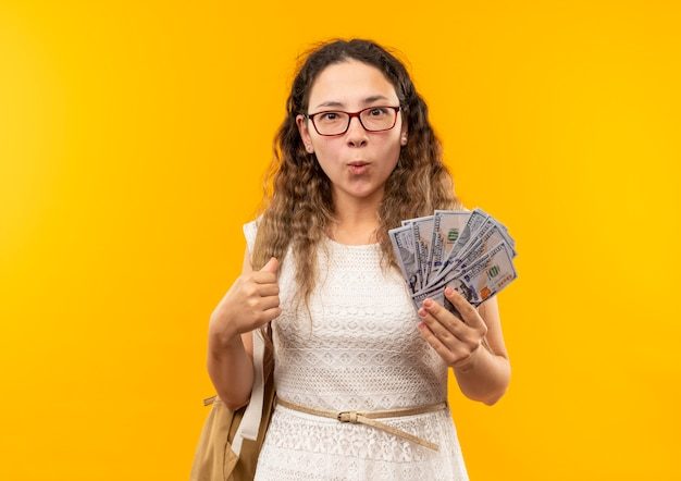 Pod wrażeniem młoda ładna uczennica w okularach iz powrotem trzyma pieniądze na żółtym tle