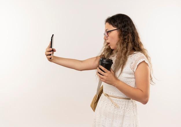 Pod wrażeniem młoda ładna uczennica w okularach iz powrotem trzymając i patrząc na telefon komórkowy z plastikową filiżanką kawy w ręku na białym tle na