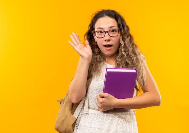 Pod wrażeniem młoda ładna uczennica w okularach iz powrotem trzymając książkę pokazując pustą dłoń na żółtym tle