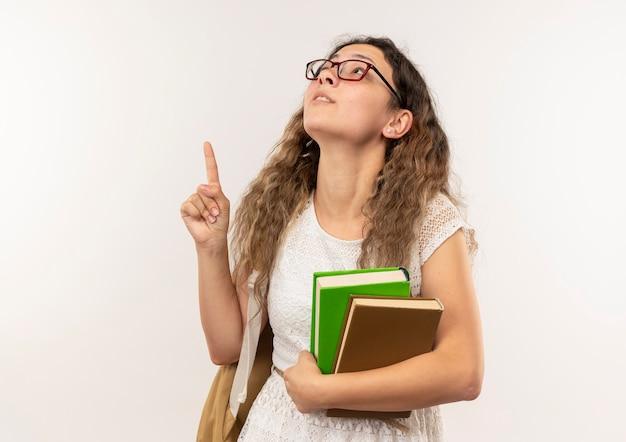 Pod wrażeniem młoda ładna uczennica w okularach iz powrotem trzymając książki patrząc i wskazując w górę na białym tle
