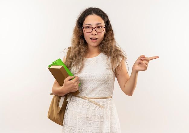 Pod wrażeniem młoda ładna uczennica w okularach iz powrotem trzymając książki, wskazując na bok na białym tle