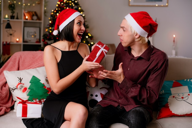 Pod wrażeniem młoda para w domu w czasie świąt bożego narodzenia w czapce świętego mikołaja siedzi na kanapie w salonie i odbiera prezenty