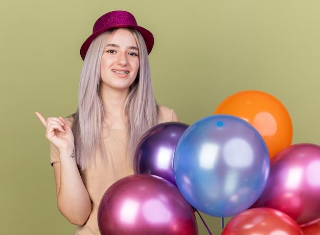 Pod wrażeniem młoda piękna dziewczyna nosząca aparat ortodontyczny z czapką stojącą za balonami, wskazującymi z boku
