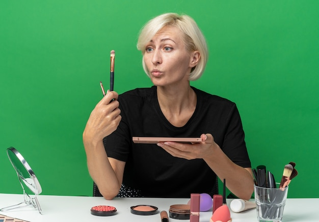 Pod wrażeniem młoda piękna dziewczyna siedzi przy stole z narzędziami do makijażu, nakładającymi cień do powiek z pędzlem do makijażu na zielonej ścianie