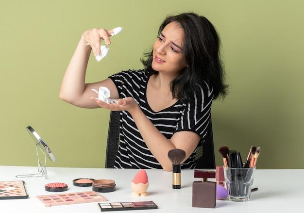 Pod wrażeniem młoda piękna dziewczyna siedzi przy stole z narzędziami do makijażu, trzymając i patrząc na krem do włosów odizolowaną na oliwkowozielonej ścianie