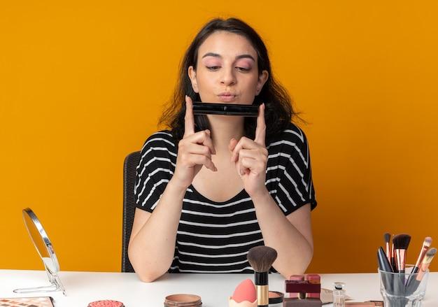 Pod wrażeniem młoda piękna dziewczyna siedzi przy stole z narzędziami do makijażu, trzymając i patrząc na pędzel do pudru na białym tle na pomarańczowej ścianie