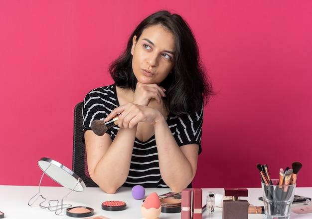 Pod wrażeniem młoda piękna dziewczyna siedzi przy stole z narzędziami do makijażu, trzymając pudrowy rumieniec, kładąc rękę pod brodą odizolowaną na różowej ścianie