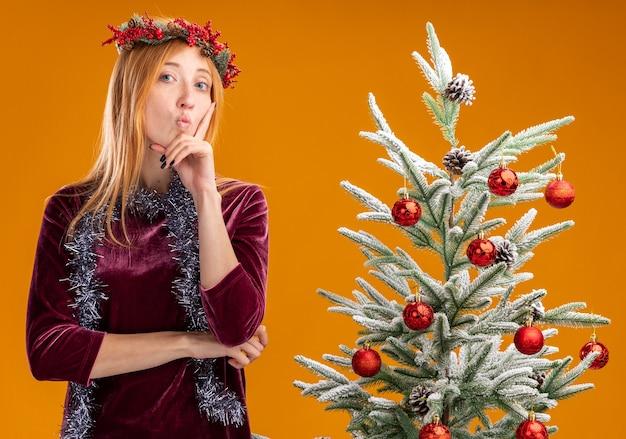 Pod wrażeniem młoda piękna dziewczyna stojąca w pobliżu choinki ubrana w czerwoną sukienkę i wieniec z girlandą na szyi kładąc palec na policzku na białym tle na pomarańczowym tle