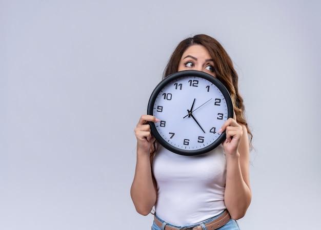 Pod wrażeniem młoda piękna dziewczyna trzyma zegar i chowając się za nim patrząc na prawą stronę z miejsca na kopię