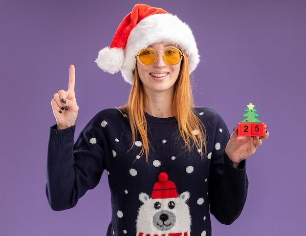 Pod wrażeniem młoda piękna dziewczyna ubrana w świąteczny sweter i kapelusz w okularach trzyma świąteczne zabawki punkty w górę na białym tle na fioletowym tle