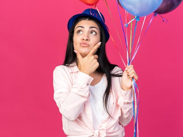 Pod wrażeniem młoda piękna dziewczyna w imprezowym kapeluszu trzymająca balony chwyciła podbródek