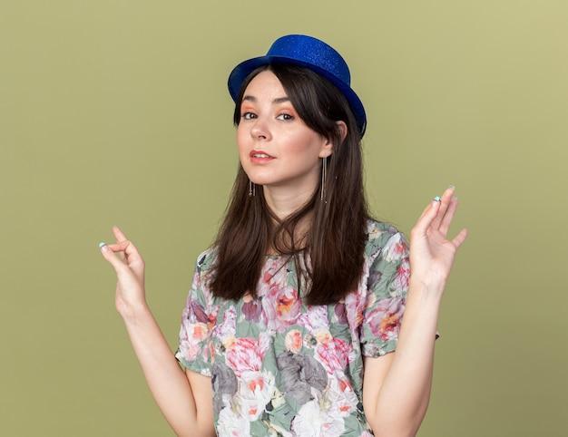 Pod wrażeniem młoda piękna dziewczyna w kapeluszu imprezowym pokazującym w porządku gest