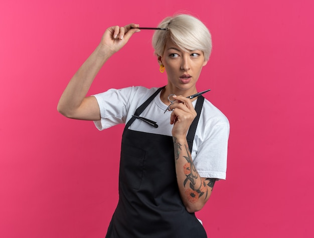 Pod wrażeniem młoda piękna kobieta fryzjerka w mundurze trzymająca nożyczki z grzebieniem odizolowanym na różowej ścianie