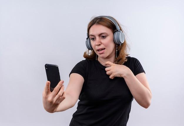 Pod wrażeniem młoda przypadkowa kobieta nosi słuchawki i trzyma telefon komórkowy na odosobnionej białej przestrzeni