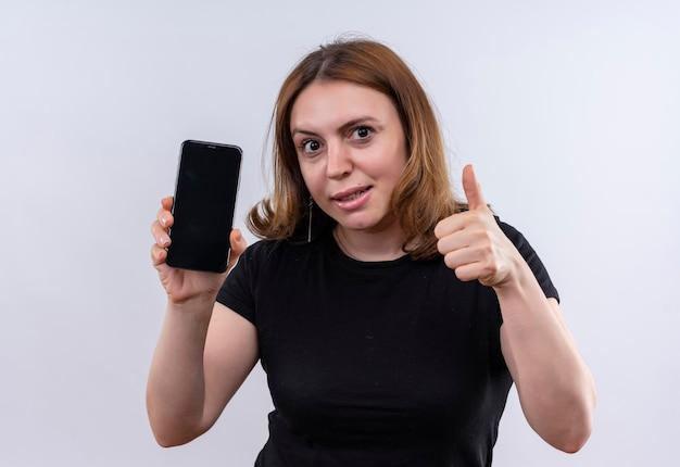 Pod wrażeniem młoda przypadkowa kobieta trzyma telefon komórkowy i pokazuje kciuk do góry na odosobnionej białej przestrzeni