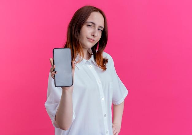Pod wrażeniem młoda ruda dziewczyna trzyma telefon i kładzie rękę na biodrze na białym tle na różowym tle